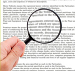 Hand holding magnifying glass reading important document