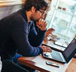 man using computer in cafe