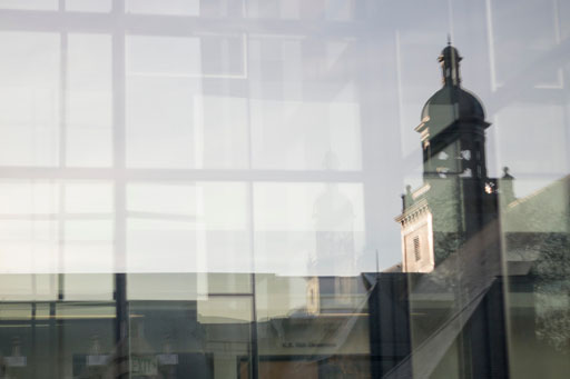 Photo by Katherine Turner. Reflection of the Denny Hall bell tower in the windows of PACCAR Hall Business School.