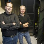 Photo of two men standing in front of Hyak supercomputer