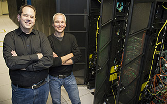 Jeff Gardner and Chance Reschke stand next to the Hyak supercomputer.