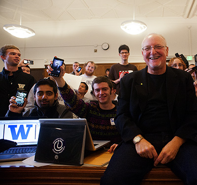Professor in front of class with students holding up cell phone