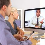 Two people video conferencing with another person