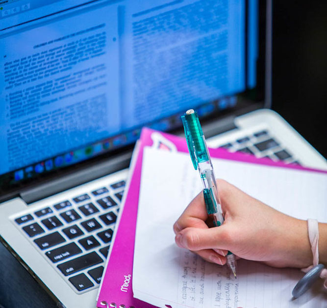 Doing homework with laptop alongside laptop