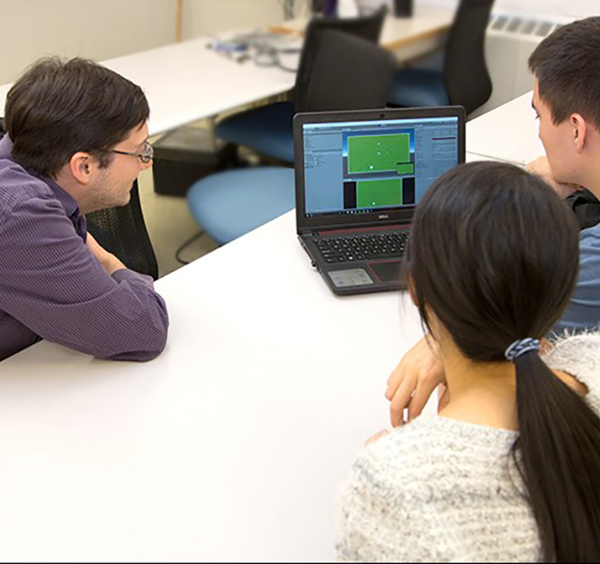 Instructor with two students looking at a video game