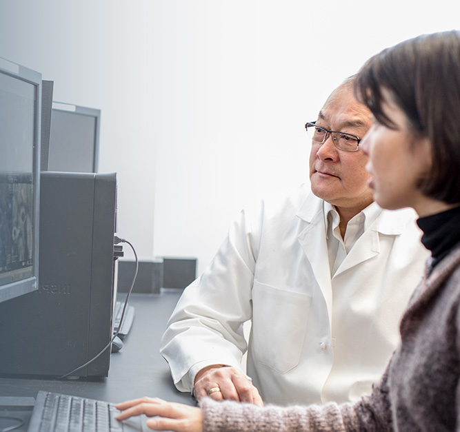 two people work together in front of a computer