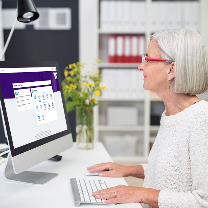 Woman looking at computer with screenshot of new Workday interface