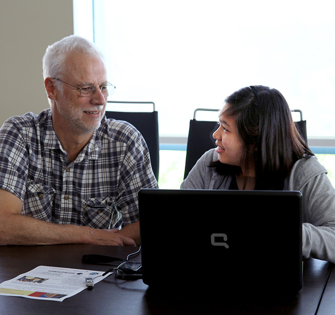 Teacher working with student at a computer