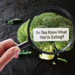 Hand with magnifying glass over Do You Know What You're Eating? food label on broccoli