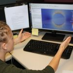 Student looking at computer screen with simulation produced using Hyak