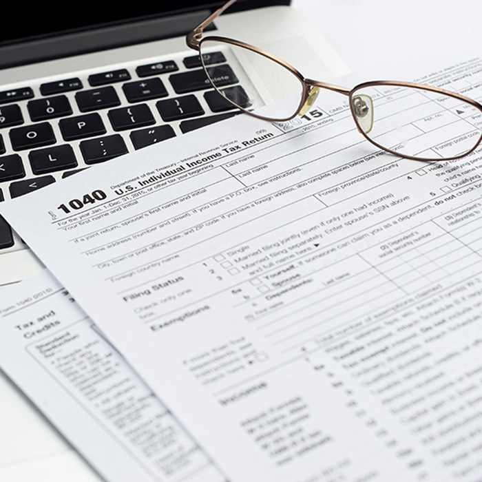 U.S. 1040 income tax return form with laptop and glasses