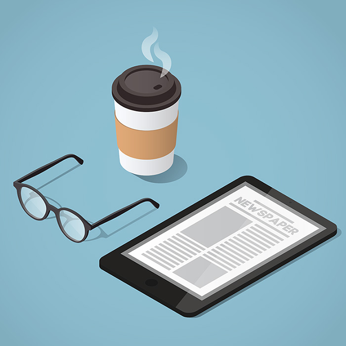 digital newspaper concept with a pair of glass and a to-go cup with a hot beverage
