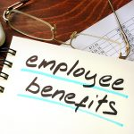 Employee benefits written on a notepad.