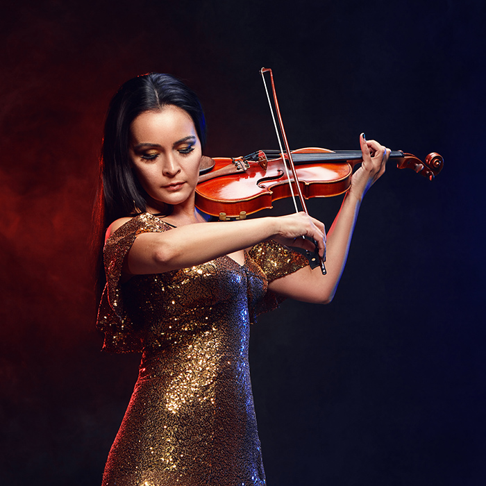 Violinist woman performs on stage.