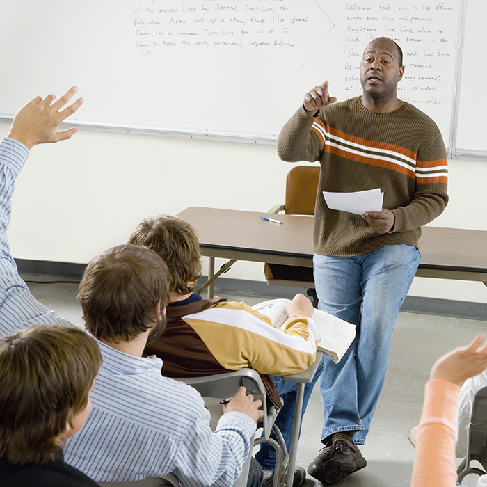 Professor pointing at college student with hands raised in classroom