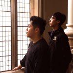 Alex Mooc and Brandon Mar stand facing a window