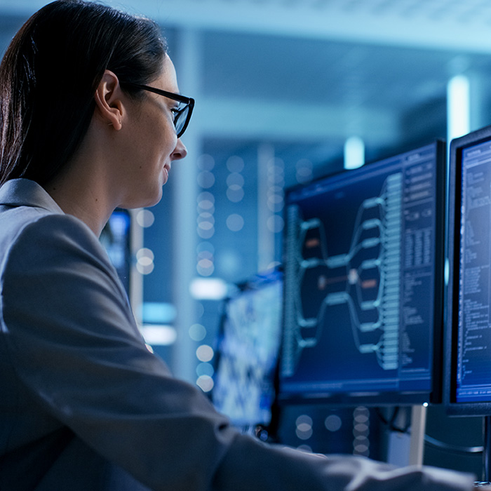 Woman monitoring multiple computer displays