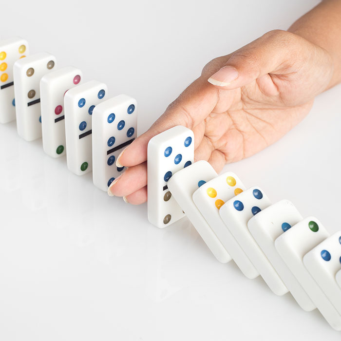 Human hand stopping a line of dominoes from falling. concept image for recovery plan