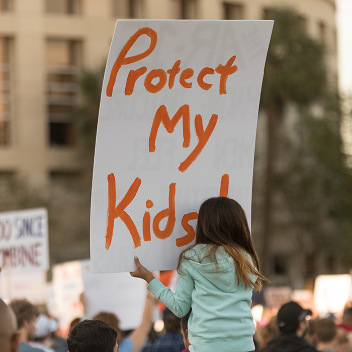 """Little Girl Holding a """"Protect My Kids"""" Sign"""