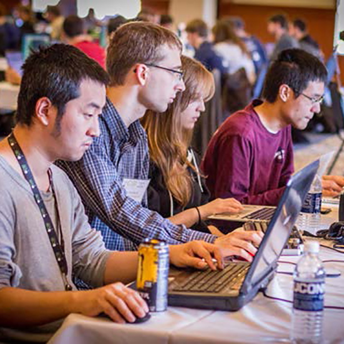 Four students work on their computers at a Capture the Flag cyber warfare competition
