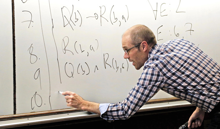 A man writing equations on a whiteboard.