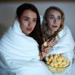 Two girls wrapped into blanket eating corn cheerios and watching horror movie