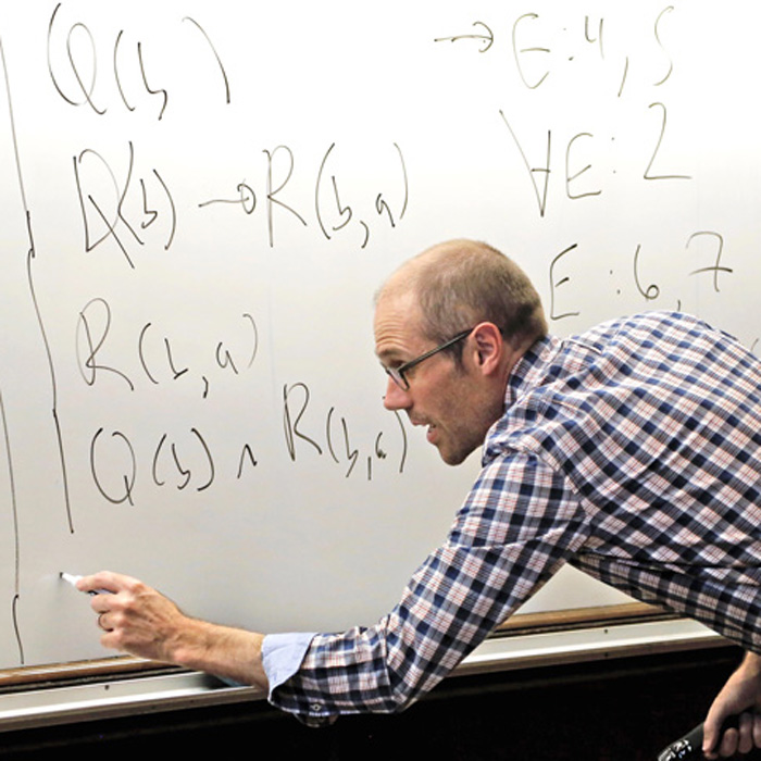 UW instructor Ian Schnee teaching, writing on a whiteboard