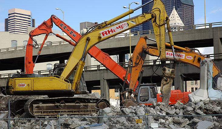 Heavy machinery on top of concrete rubble in front of the Seattle viaduct