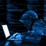 Hacker in a blue hoody standing in front of a code background with binary streams and information security terms