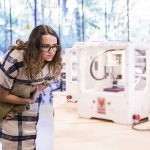 Woman looks at a 3D printer at The Mill