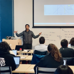 Instructor teaches the Deep Learning Institute in front of people seated in a classroom