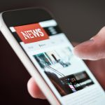 news site on mobile phone held in hand