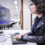 Woman types at a computer