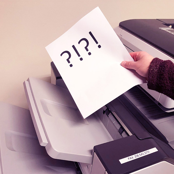 A fax with ?!?! comes out of the fax machine