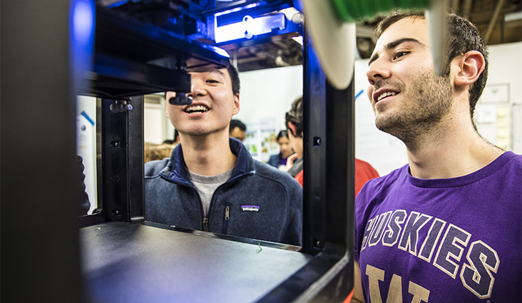 Image of two people in front of a 3D printer