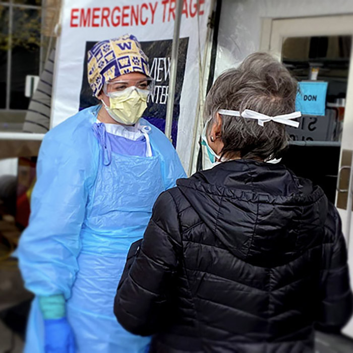 A medical professional in personal protective equipment talks to a patient in a mask outside a triage tent for evaluating potential COVID-19 cases